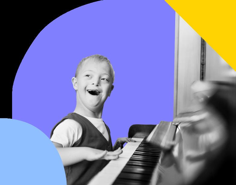 Boy sitting at a piano, smiling.