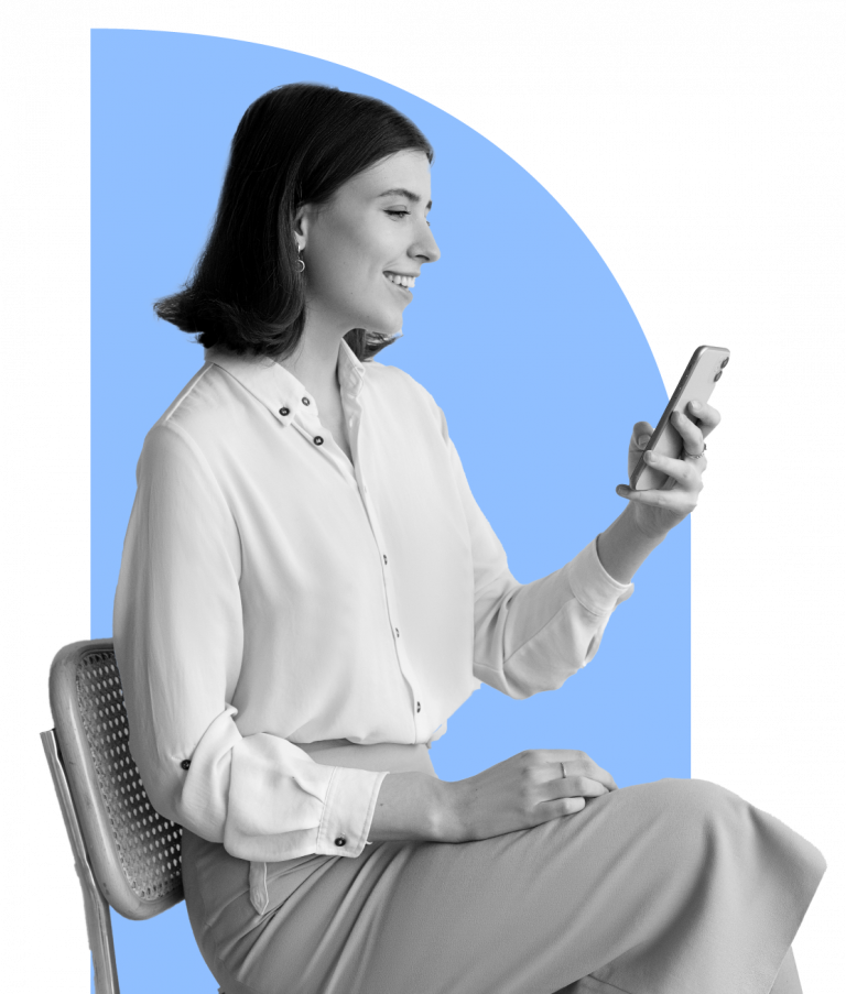 Woman sitting on chair smiling while looking at mobile phone.