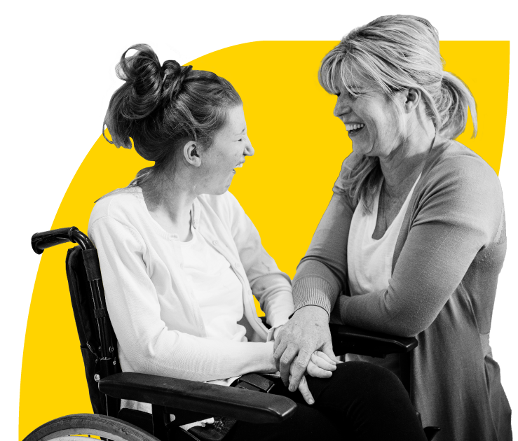 Woman in wheelchair holding hands and laughing with woman kneeling next to her.