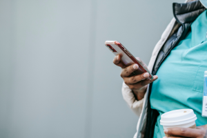 woman in scrubs using cell phone